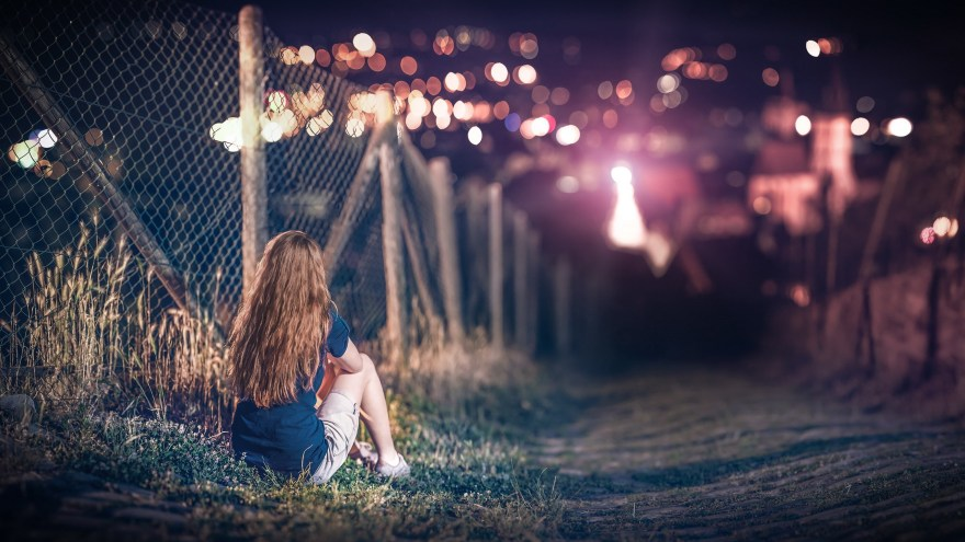 blonde-girl-sitting-in-field-road-looking-night-lights-bokeh